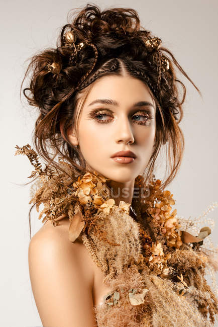 Attractive fashionable woman with golden makeup and wreath looking away — Stock Photo