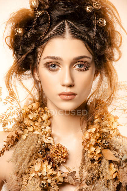 Attractive fashionable woman with golden makeup and wreath looking at camera — Stock Photo