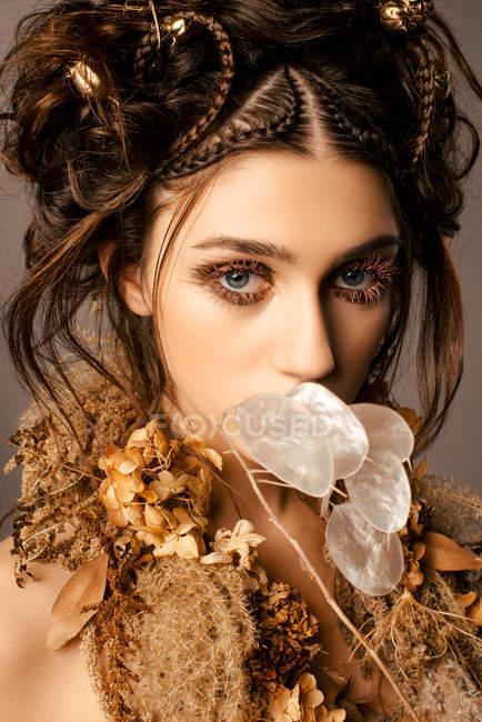 Привлекательная модная женщина с золотым макияжем и венком, смотрящая в камеру — стоковое фото