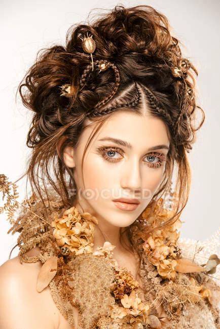 Attraente donna alla moda con trucco dorato e ghirlanda guardando macchina fotografica — Foto stock