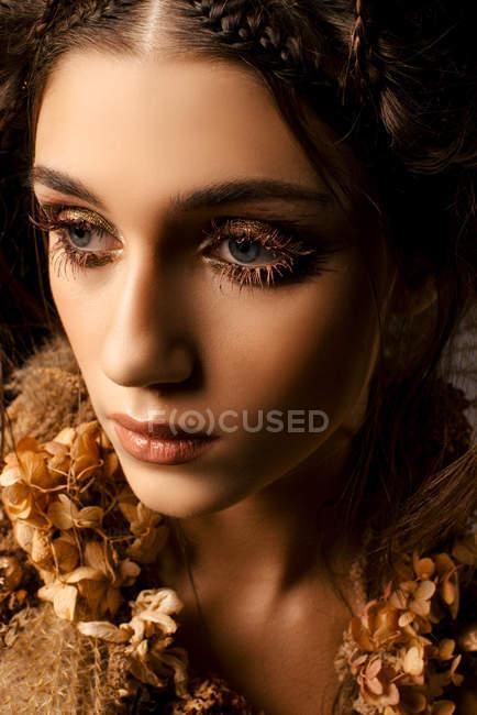 Привлекательная модная женщина с золотым макияжем и венком, смотрящая в сторону — стоковое фото