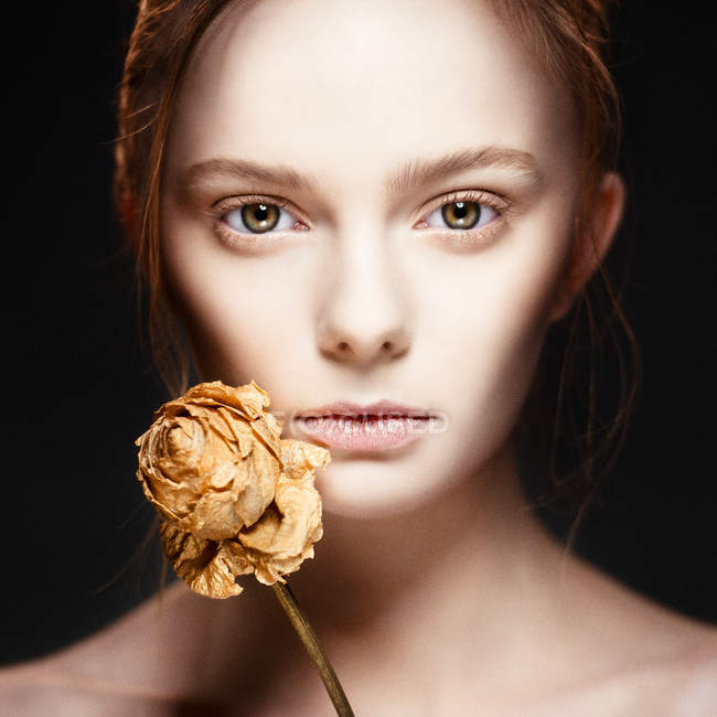 Fashionable woman with creative make up  posing wit dry flower — Stock Photo