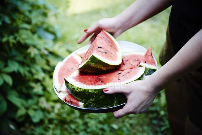 Mãos femininas segurando melancia fatiada — Fotografia de Stock