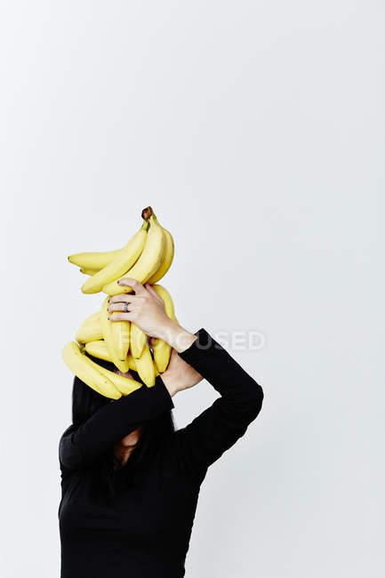 Woman hiding face under bananas — Stock Photo