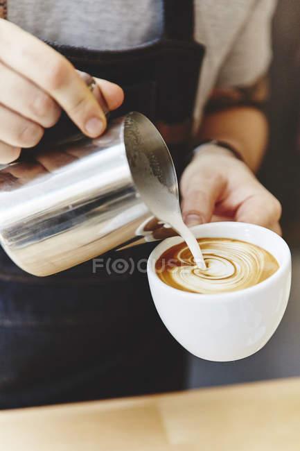Бариста в фартуке делает кофе — стоковое фото