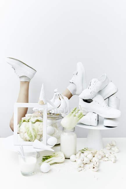 Piernas femeninas y sanos ingredientes blanco - foto de stock