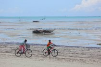Boys Riding Bikes on the beach Zanzibar — Stock Photo