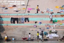 Pessoas e roupas lavadas secando à luz do sol nos ghats em Varanasi, Índia . — Fotografia de Stock