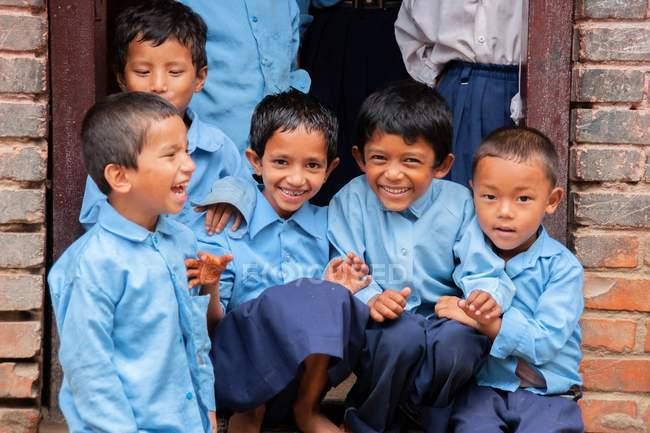 Niños en uniforme escolar sonriendo a la cámara - foto de stock
