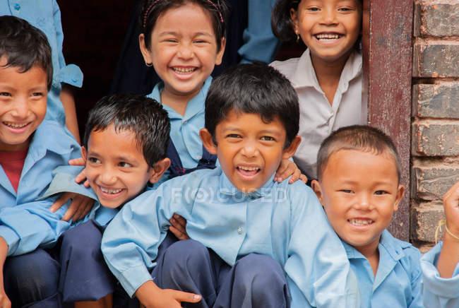 Crianças de uniforme escolar sorrindo para a câmera — Fotografia de Stock