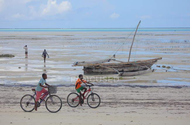 Хлопчики їзда велосипеди на пляжі Занзібар — стокове фото