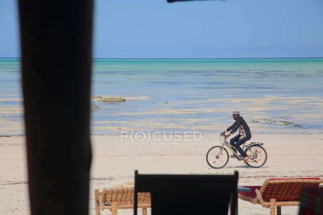 Людина їзда Байк на пляжі Занзібар — стокове фото