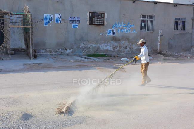 Місцевим чоловік змітайте вулиці, острів Hormoz, Іран — стокове фото