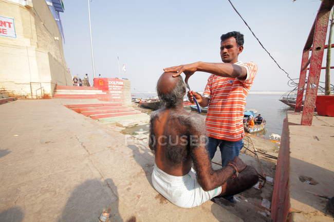 People shaving near  Ganges river in  Varanasi Old City. — Stock Photo