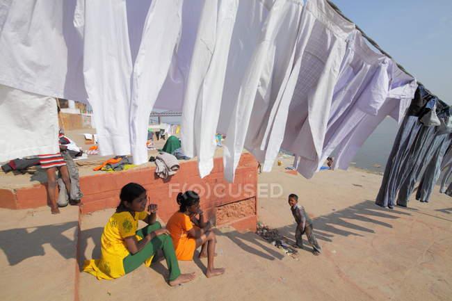 Indische Kinder und gewaschene Kleidung, die in den Ghats in Varanasi, Indien, im Sonnenlicht trocknet. — Stockfoto