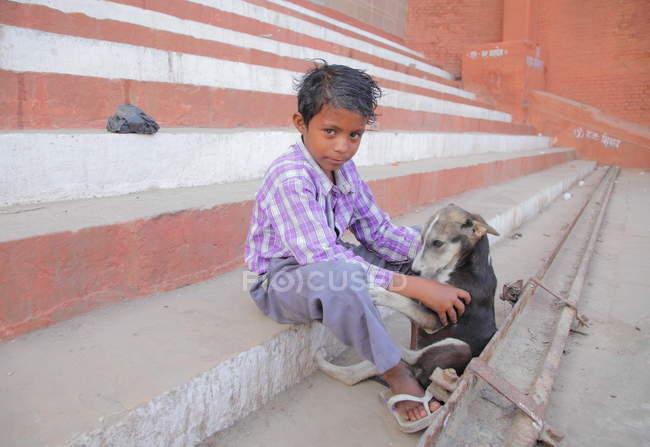 Ritratto del piccolo ragazzo e cane indiano sulla strada della città . — Foto stock