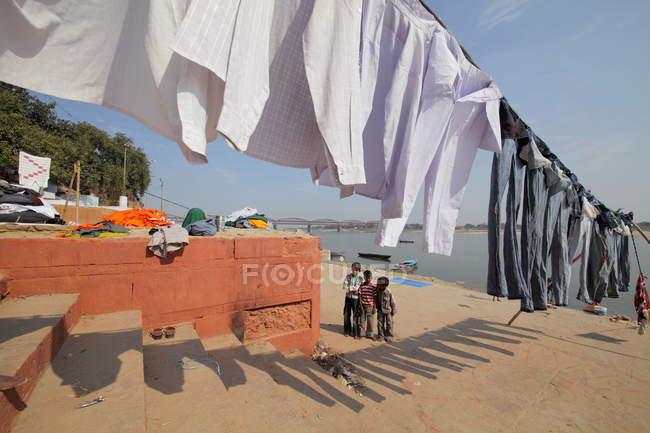 Bambini indiani e vestiti lavati che si asciugano alla luce del sole ai ghats a Varanasi, India . — Foto stock