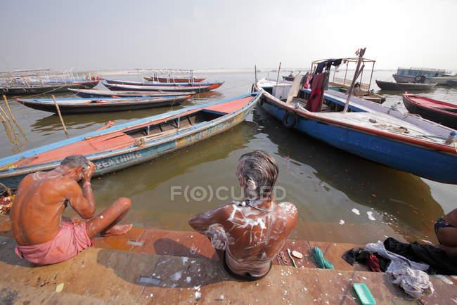Persone lavare e fare il bagno nel fiume Gange nella città vecchia di Varanasi . — Foto stock