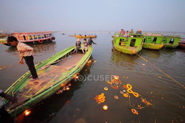 Leute und brennende Lampen im heiligen Wasser des Heiligen Ganges — Stockfoto