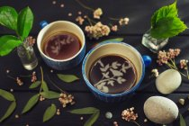 Cups of tea with Gardener's leaves — Stock Photo