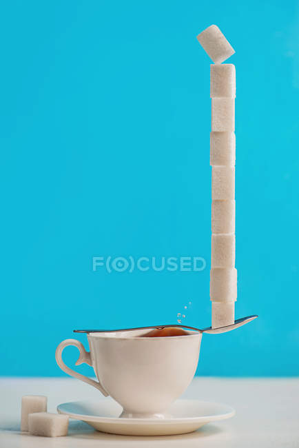 Cup with spoon with stack of sugar — Stock Photo