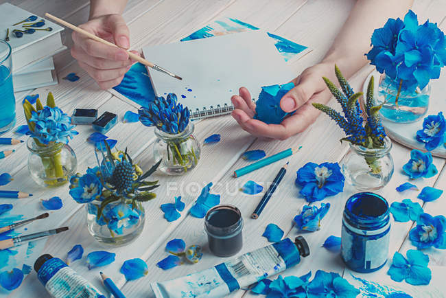 Hands with blue paint brush — Stock Photo