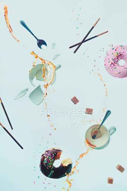 Tassen Kaffee Spritzer mit Donuts im Flug — Stockfoto