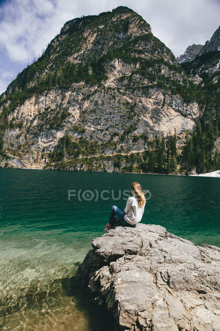 Young woman sitting on cliff near lake — Stock Photo