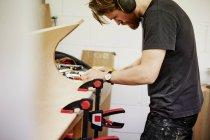 Людина в workbench працює над шматок вигнутий дерева — стокове фото