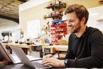 Homem sentado usando um laptop . — Fotografia de Stock