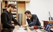 Dos personas discutiendo un diseño - foto de stock
