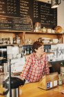 Woman in a plaid shirt working behind the counter — Stock Photo