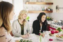Mujeres en la cocina preparando alimentos frescos - foto de stock