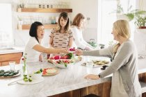 Women in a kitchen preparing lunch — Stock Photo