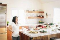 Frau in der Küche durch einen Zähler — Stockfoto