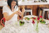 Femme à l'aide de serveurs de salade pour charger son assiette — Photo de stock