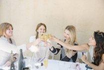 Quatro mulheres sorridentes, sentado em uma mesa — Fotografia de Stock