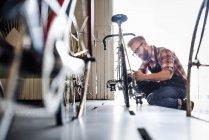 Man in bicycle repair shop. — Stock Photo