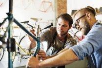 Uomini che guardano una bicicletta . — Foto stock