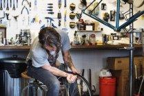 Riparazione uomo in un negozio di biciclette . — Foto stock