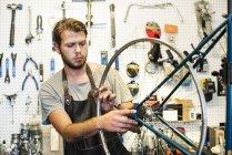 Мужчина ремонтирует велосипедный магазин . — стоковое фото