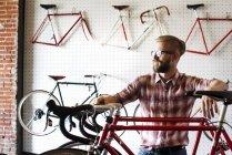 Боковой вид человек в магазин велосипедов — стоковое фото
