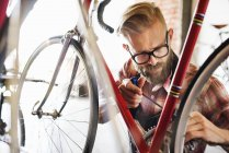 Man repairing bicycle in shop — Stock Photo