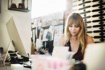 Donna seduta in un ufficio a una scrivania — Foto stock