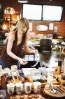 Mulher, organizando a mercadoria em uma tabela — Fotografia de Stock