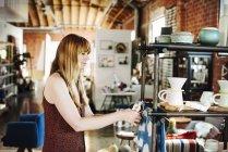 Жінка організацію товарів на полиці. — стокове фото