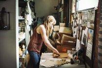 Mujer envolviendo mercancía en papel marrón. - foto de stock