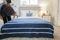 Woman smoothing a blue striped throw over — Stock Photo