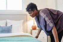 Женщина курит бросок над двуспальной кроватью — стоковое фото