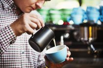Man pouring hot milk into a cup of coffee — Stock Photo